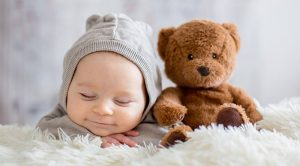 Schlafendes Baby mit Bär, schlafen lernen